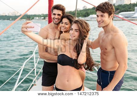 Smiling happy friends standing on yacht deck and making selfie