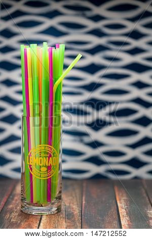 Multicolored drinking straws in a lemonade glass on wood surface