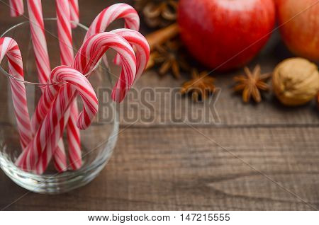 Peppermint Candy Canes and other Christmas decorations on wooden background, selective focus, copy space
