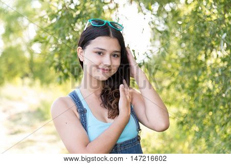 Teen girl standing on a wood background