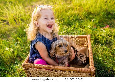 happy child girl with her dog sitting in a wicker basket at sunset