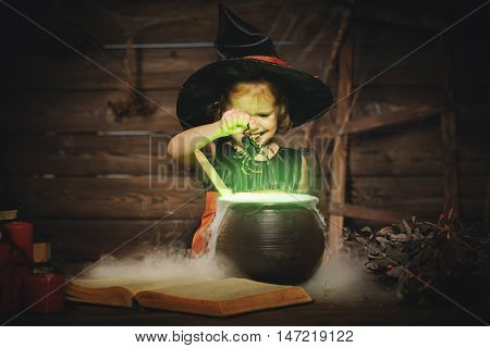 Halloween. child girl witch preparing a potion in the cauldron