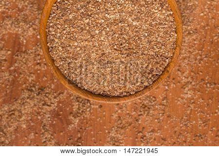 Ground Wheat into a bowl over a wooden table. Trigo para quibe. Kibbeh