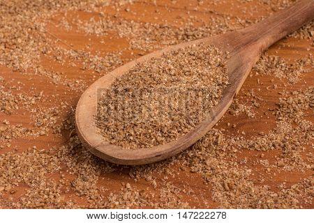 Ground Wheat into a spoon over a wooden table. Trigo para quibe. Kibbeh