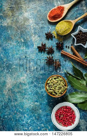 Spices On Blue Stone Background With Space For Text.