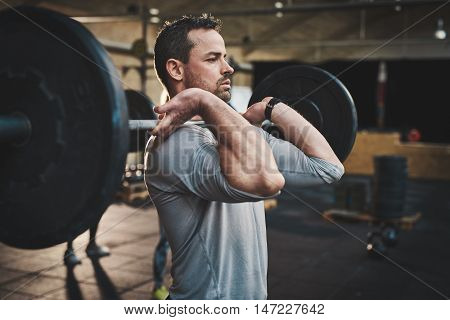 Tough bearded man with thick muscular arms and gray shirt pulling up large barbell in fitness training class indoors
