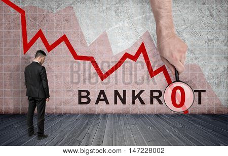 Back view of a businessman standing on the background of falling diagram with big man's hand with a magnifier and 'bankrot' inscription. Stock market selloff. Financial and economic crisis.