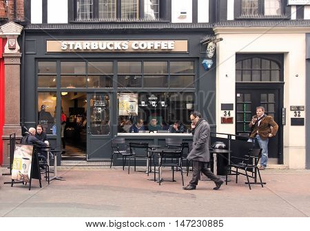 LONDON UK - March 24: Starbucks coffee shop inside Carnaby street with people having drinks inside in London UK - March 24 2016; Starbucks is an American coffee company and coffeehouse chain that operates in many locations worldwide.