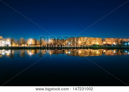 Evening Or Night View Of Urban Residential Area, Overlooks To City Lake In Illumination, Reflecting In Dark Water Surface. Navy Blue Sky Background, Gomel Homiel Belarus