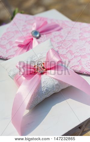 pink wedding folder and pillow with rings