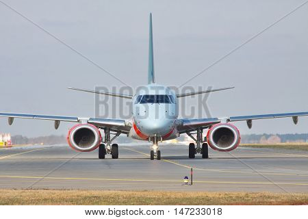 Kiev Region Ukraine - October 23 2011: Embraer ERJ-190 passenger plane on the runway front view closeup