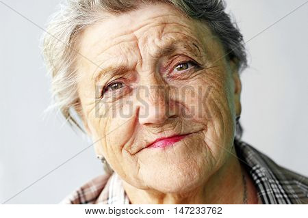 Looking old woman portrait on a grey background