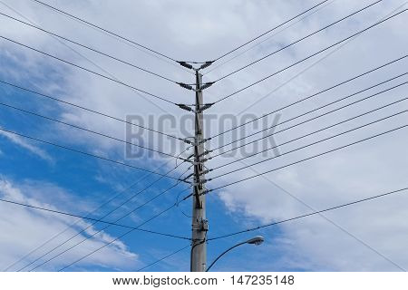 High Voltage Electric Pole and wires against blue cloudy sky