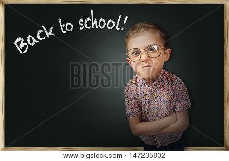 Emotional frowning pupil boy near chalkboard unhappy to return to school