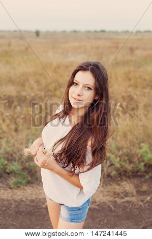 Young girl with long brown hair holds a bundle of ears in her hands smiling and looks happily. Selective focus warm tinted.