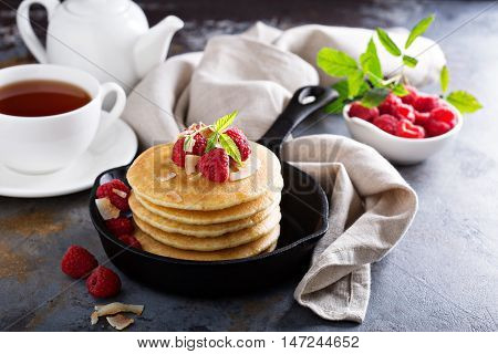 Stack of fluffy buttermilk pancakes with fresh raspberry in cast iron pen