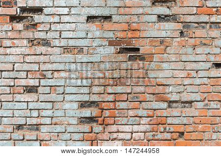 An old worn surface red brickwork wall