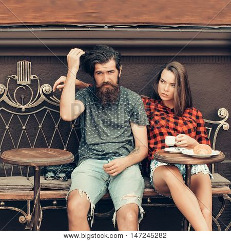 Hipster couple of pretty girl brunette and handsome man bearded sit on forged couch in vintage cafe on dark wall