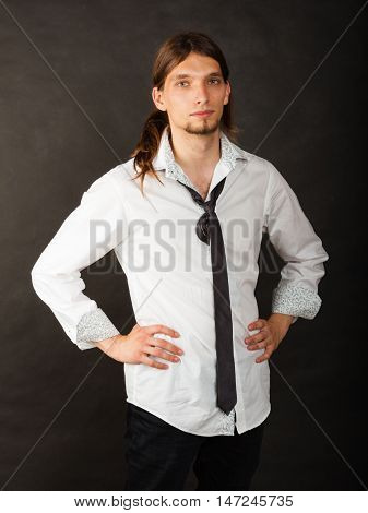 Masculinity fashion concept. Man in shirt and tie. Young long haired male on dark background.