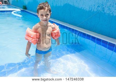 Sweet Little Boy Boy In Swimsuit With Arm Float In The Pool