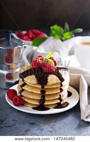Stack of fluffy buttermilk pancakes with fresh raspberry and chocolate syrup