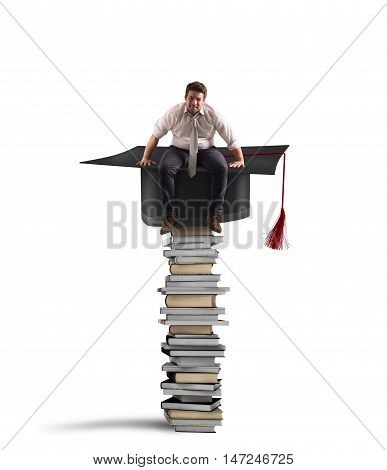 Businessman sitting on a pile of books with graduation hat