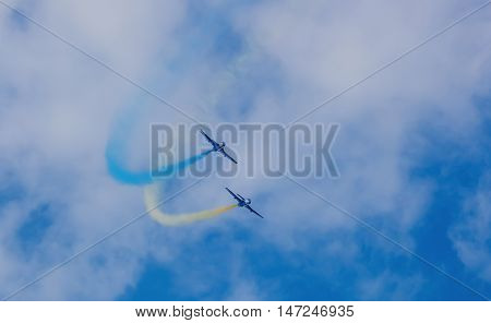 Two aircraft blue during a performance at an airshow stunt produce smoke strip of blue and yellow in the sky against a background of clouds.