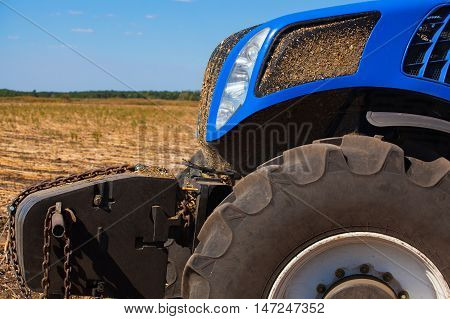 The front part of a blue tractor closeup. Agricultural machine standing in a field during plowing and harvesting soil.