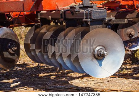 Part of the cultivator steel round discs in a row. Close-up. The work of agricultural machinery.