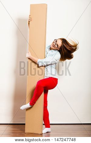 Funny Woman Moving Into Apartment Holding Box.