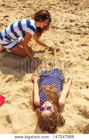 Play and fun in summer. Adorable girl daughter having fun with her mommy. Family spending time together on beach seaside.
