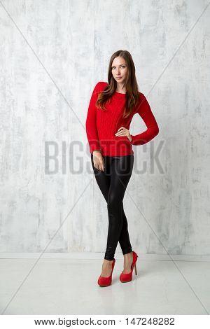 beautiful woman in red sweater in high heels posing in studio