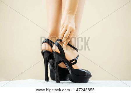Woman hand fastens strap on black shoes fancy high heel pumps strappy sandals on her beautiful legs feet on white floor