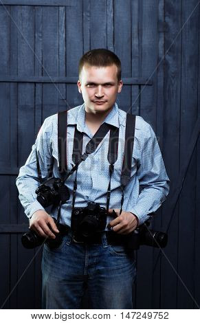 young handsome man photographer with serious face in shirt with many photo cameras equipment of journalist or reporter professional in studio on wooden background