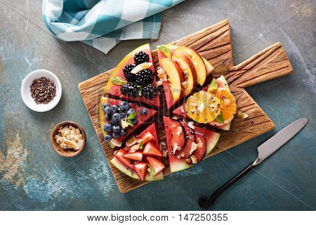 Watermelon pizza with fruits and berries, coconut flakes and cocoa nibs