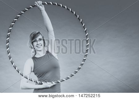 Fitness activity healthy lifestyle. Young blond woman doing exercise with hula hoop black and white photo