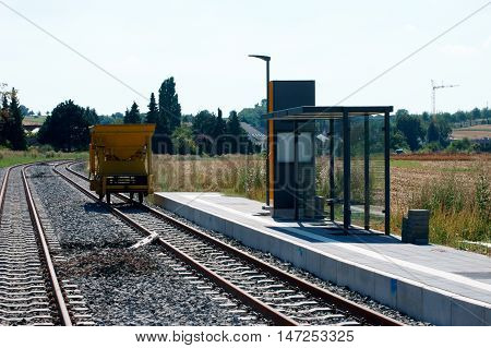 A trailer for ballast stones tools and materials standing at a newly built tram stop.