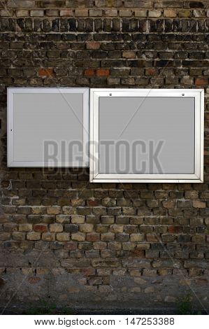 Two showcases with aluminum frame hanging on a nostalgic brick wall.