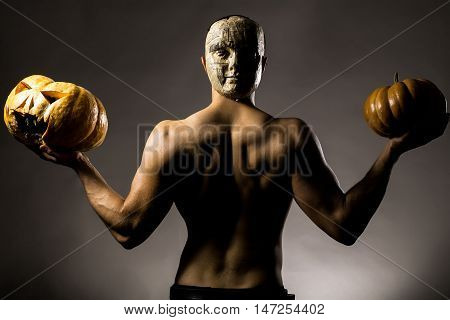 Muscular Man In Mask With Pumpkins