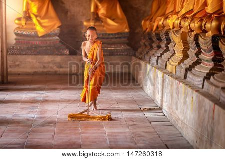 Little novices cleaning with mop the floor at Ayutthaya Historical Park in Thailand