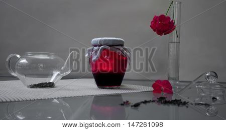Bank of raspberry jam with tea and pelargonium flower on a glass table.