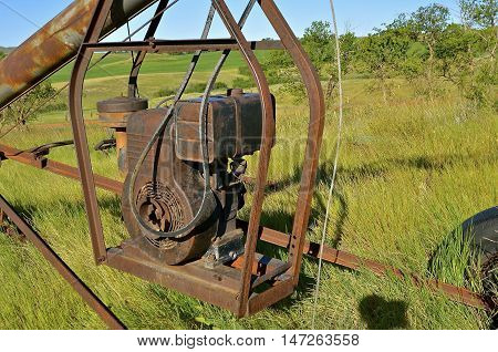 A  suspended framed gas powered engine was used to power an old rusty tube grain