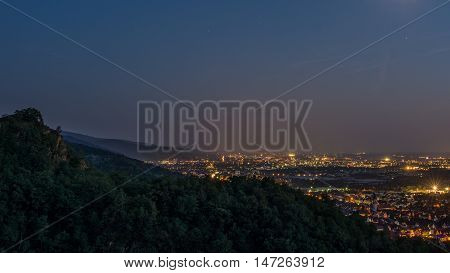 Outlook over forest hills and illuminated city