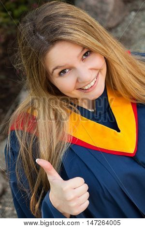 Young woman give a thumbs up in her University graduation gown