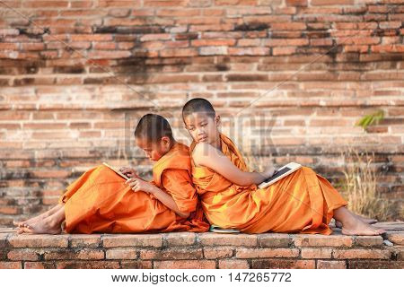 Two novice reading and studying blackboard with funny in old temple at sunset time Ayutthaya Province Thailand