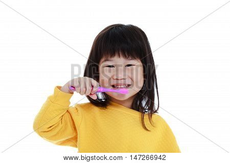 Closeup cute asian girl in pajamas with a toothbrush in hand smiling and go to brush teeth oral health concept. Isolated on white background. Chinese sleepy child waking up early in the morning.