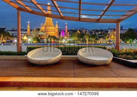 Relax corner on condominium rooftop garden with chairs on landmark bangkok Wat Arun at night background Landmark concept