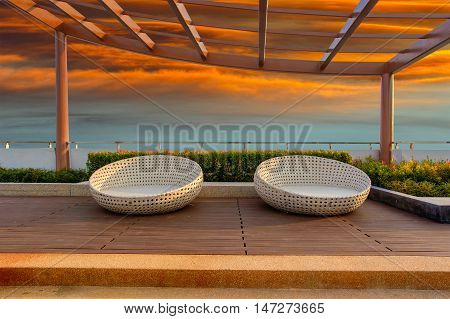 Relax corner on condominium rooftop garden with chairs on red sky sunset background