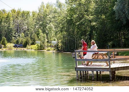 A mature wedding couple sitting on a wooden dock fishing in a natural setting