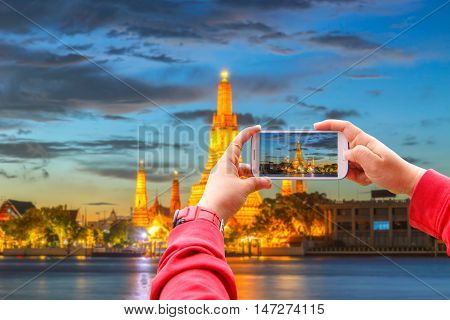 Smartphone photographing Wat Arun Buddhist religious places in twilight time Bangkok Thailand